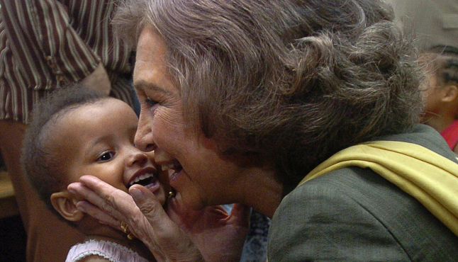 A kid smiles facing off the Queen Sofia at an event of her foundation